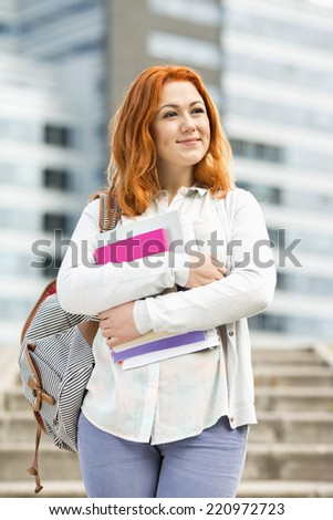 Beautiful young woman with textbooks at college campus