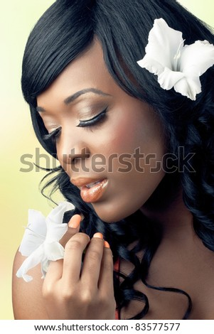 Beautiful young woman with tropical flowers in her hair and hands, close-up shot