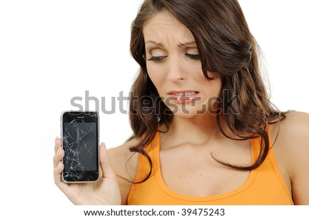 Beautiful young woman with troubled expression holding her broken touch screen mobile phone
