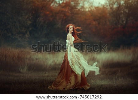 Beautiful young woman with very long red hair in a golden medieval dress walking through the autumn forest. Long red hair develops in the wind. #745017292