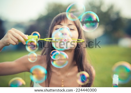 beautiful young woman with white dress blowing bubble in the city Stock foto ©