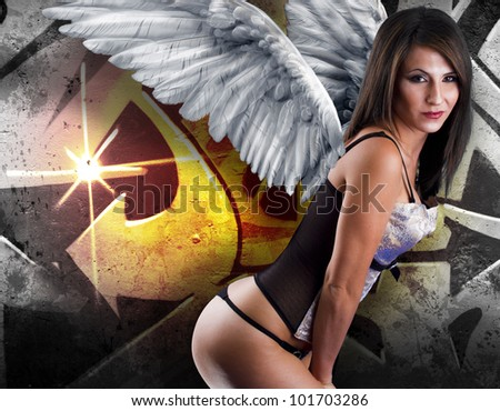 Beautiful young woman with white wings against graffiti background with intense orange light