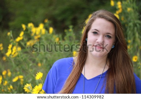 Beautiful young woman with yellow wildflowers behind her