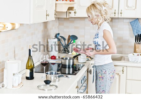 Beautiful young woman working in the kitchen