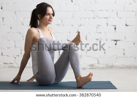 Beautiful young woman working out in loft interior, doing Seated Glute Stretch, pre-workout exercise for relieving tight muscles, warming up on blue mat during practice, full length, copy space #382870540