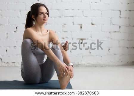 Beautiful young woman working out in loft interior, doing Seated Hip Stretch, hip opener Eka Pada Agni Stambhasana, warming up on blue mat during practice, full length, copy space