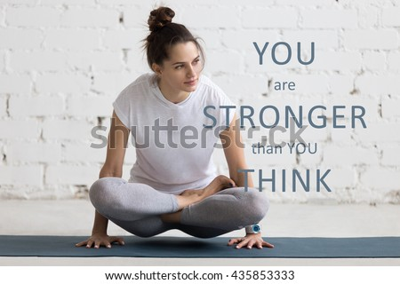 Beautiful young woman working out in loft interior, doing yoga exercise on blue mat. Motivational phrase \