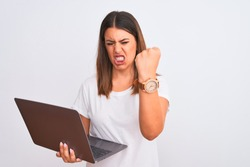 Beautiful young woman working using computer laptop over white background angry and mad raising fist frustrated and furious while shouting with anger. Rage and aggressive concept.