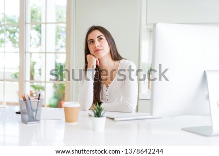 Beautiful young woman working using computer with hand on chin thinking about question, pensive expression. Smiling with thoughtful face. Doubt concept.