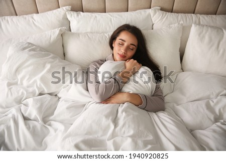 Beautiful young woman wrapped with soft blanket sleeping in bed at home, above view Stock photo ©