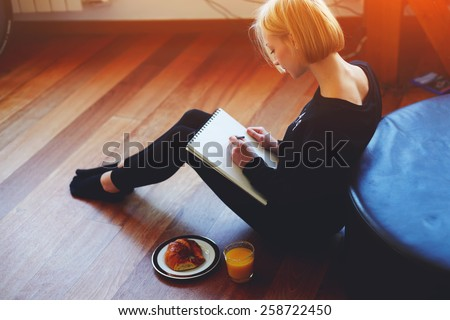 Stock Photo Beautiful young woman writing something in the note pad while sitting on the floor at living room, charming female studying doing homework at home, girl writes diary at her breakfast, flare light
