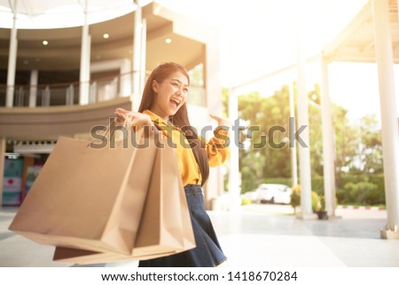Beautiful young women, beaming with shopping bags in department stores.
