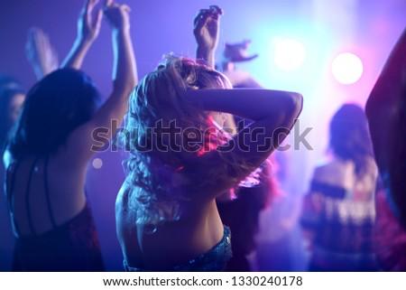 Beautiful young women dancing in night club