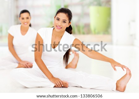 Beautiful young women doing stretching exercise - stock photo