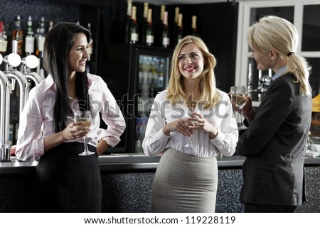 Beautiful young women enjoying a glass of wine after work at a bar.