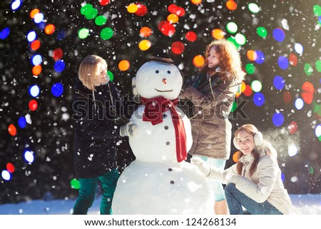 Beautiful young women enjoying building a snowman on a snowy winter day, blurred lights on background