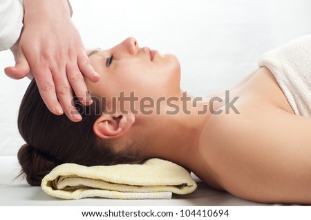 Beautiful young women getting a face massage in massage salon.
