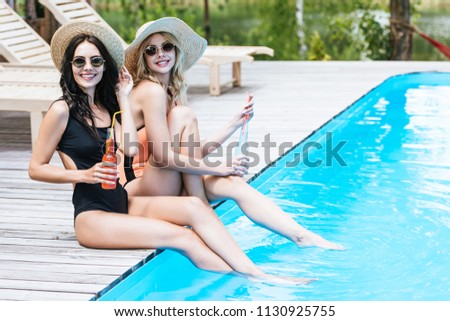 beautiful young women in swimsuits and hats holding bottles with summer drinks and smiling at camera near pool
