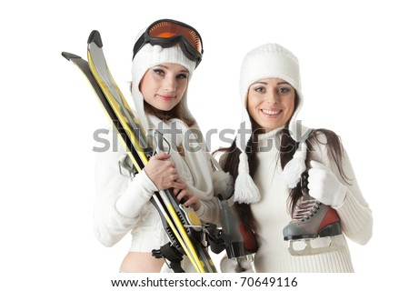 Beautiful young women in winter clothes with skates and skis  on a white background. Winter sports.