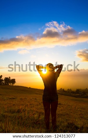 Beautiful young women looking out over Hawaiian sunset