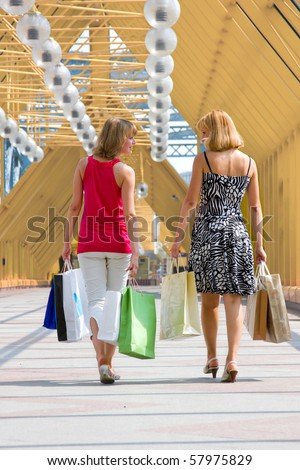 Beautiful young women shopping. Young woman holding several bags in shopping centre. Two friends on a shopping tour in the city - stock photo