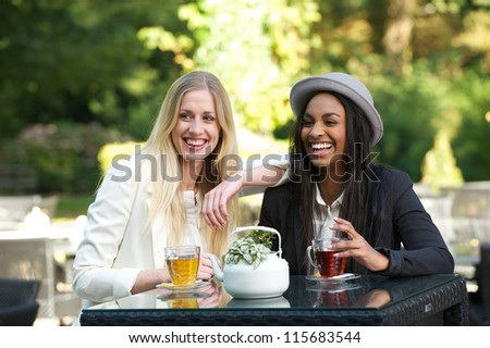 Beautiful young women smiling and drinking tea at an outdoors cafe