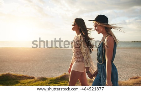 Shutterstock Beautiful young women strolling on a beach. Two friends walking on the beach on a summer day, enjoying vacation.