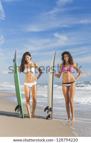 Beautiful young women surfer girls in bikinis with surfboards on a beach