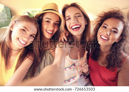 Beautiful young women taking selfie in car