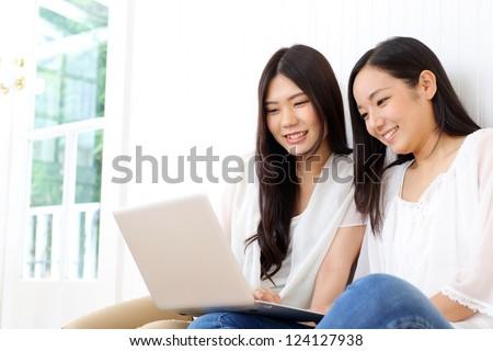 Beautiful young women using a laptop computer. Portrait of asian
