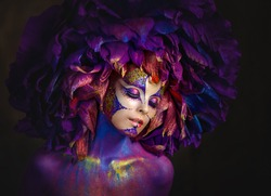 Beautiful young women with a lilac flower. Bright purple flower girl. Girl flower Fantasy girl with a flower on her head. Fantasy girl with very long nails