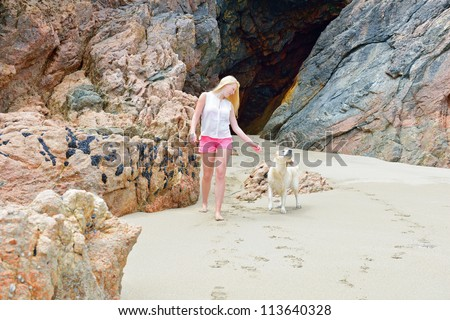 Beautiful young women with dog on the beach - stock photo