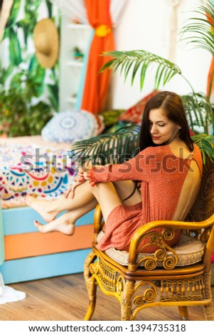 Beautiful young young woman sitting on a in a rattan chair in a tropical african hotel room with a colorful interior enjoying a vacation. Summer vacation begins.