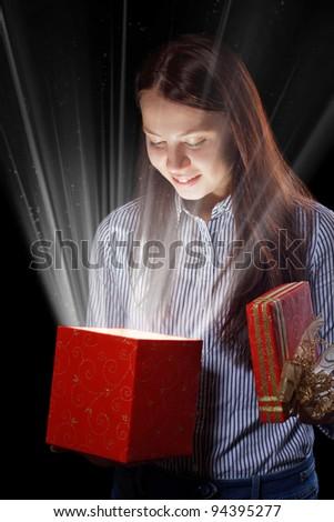 beautifull girl opening gift box. Black background