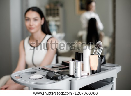 Beautifull lady sitting in beauty zone. Focus on professional expensive cosmetic