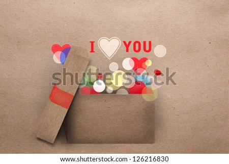 Beautifull natural paper applique Valentine greeting card with an open gift box emitting round party lights and the message Love you with a symbolic heart and copyspace - stock photo