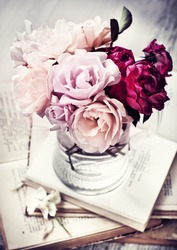 Beautifull Roses in a glass vase with books in vintage style