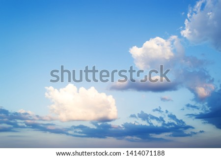 Beautifull skyscape at evening. Fluffy white and blue clouds high in a bright blue sky. Crystal clear air and good weather. Tranquil background. #1414071188