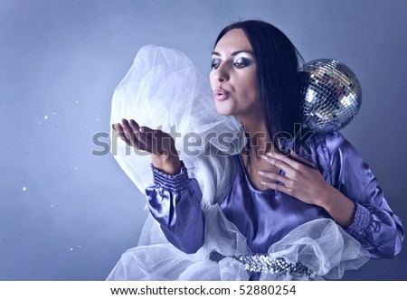 Beautifull woman stylised on club fairy blowing off from palm silver spangles. Fashion Photo.