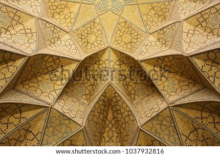 Beautifully and intricately ornamented ceiling in warm yellow colors with blue hues in a muslim mosque in Esfahan, Iran.