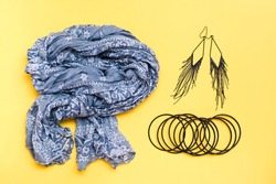 Beautifully curved cotton neck scarf, bracelets and earrings on a yellow background. Spring outfit, fashion accessories