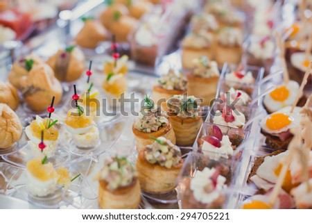 Beautifully decorated catering banquet table with different food snacks and appetizers with sandwich, caviar, fresh fruits on corporate event or wedding celebration