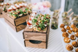 Beautifully decorated catering banquet table with different food snacks and appetizers with sandwich