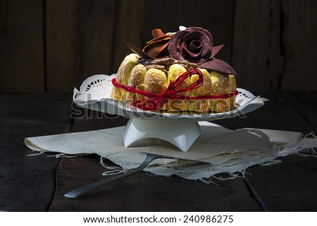 Beautifully decorated chocolate cake topped with roses on cocoa icing and surrounded with freshly baked golden pastries for a delicious dessert or sweet