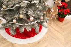 Beautifully decorated Christmas tree with skirt indoors