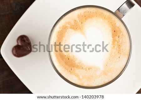 BEAUTIFULLY DECORATED CUP OF CAPPUCCINO AND CHOCOLATE HEART, AGAINST POLISHED TABLE TOP