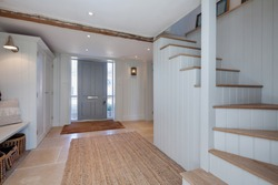 Beautifully decorated in a contemporary style this chic residential enytrance hall has eggshell blue panelled walls, bench seat, doorway, large rug and stairs