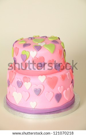 Beautifully decorated round double tier birthday cake with pink fondant plastic icing and pink, green, white and purple hearts all over, on a cream background