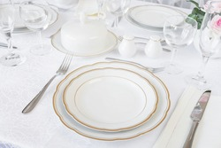 Beautifully decorated table with empty white plates, glasses, cutlery and flowers on luxurious tablecloths