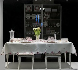 Beautifully decorated table with white plates, crystal glasses, linen napkin, cutlery and tulip flowers on luxurious tablecloths. shop window. night scene